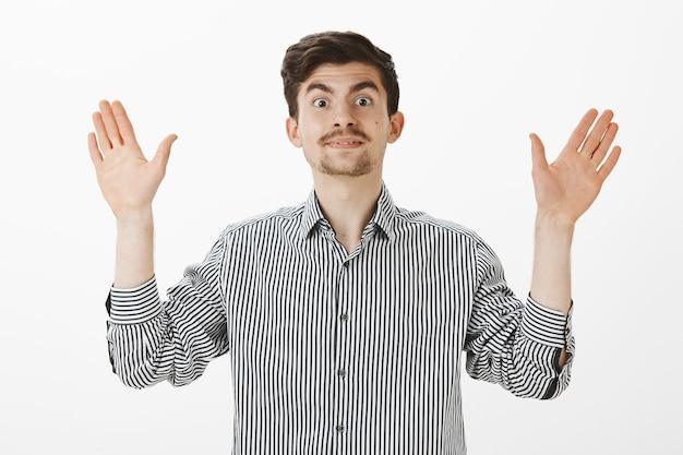 Kryty ujęcie emocjonalnego, przyjaznego, zabawnego faceta z brodą i wąsami, unoszącego dłoń w geście poddania się lub pragnącego oklaskiwać, czującego się zadowolonym i szczęśliwym otrzymującym dobry odpoczynek, stojącego nad szarą ścianą