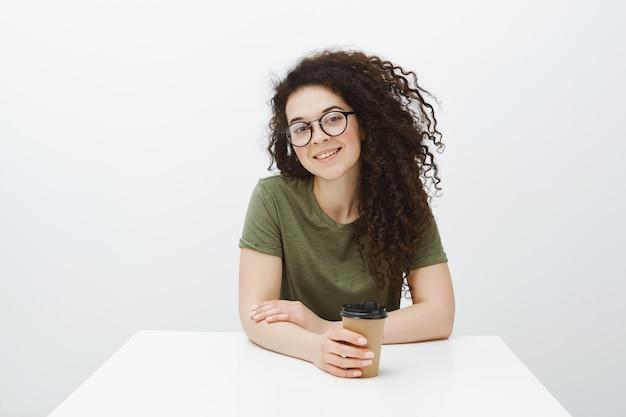 Kryty ujęcie kreatywnej, przystojnej kobiety z kręconymi włosami w okularach, siedzącej przy stole i pijącej kawę, uśmiechającej się szeroko