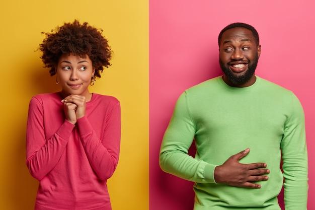 Kryty ujęcie ładnej kobiety spogląda z rozmarzonym wyrazem na bok, trzyma rękę pod brodą, szczęśliwy brodacz zadowolony po zjedzeniu kolacji, trzyma ręce na brzuchu, czuje sytość, jest w dobrym nastroju