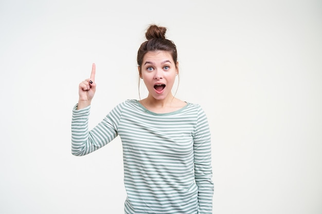 Kryty ujęcie młodej atrakcyjnej brunetki kobiety z przypadkową fryzurą, podnoszącą emocjonalnie rękę, jakby miała pomysł i zdumiewająco patrząc z przodu, odizolowane na białej ścianie