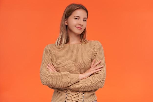 Kryty ujęcie młodej atrakcyjnej kobiety ubranej w beżowy sweter z założonymi rękami na piersi, pozując nad pomarańczową ścianą, mrużąc oczy i sprytnie patrząc z przodu
