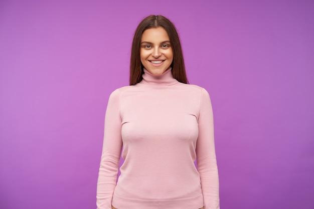 Kryty ujęcie młodej długowłosej brunetki patrzącej pozytywnie z przodu z uroczym uśmiechem, trzymając ręce w dół, stojąc nad fioletową ścianą
