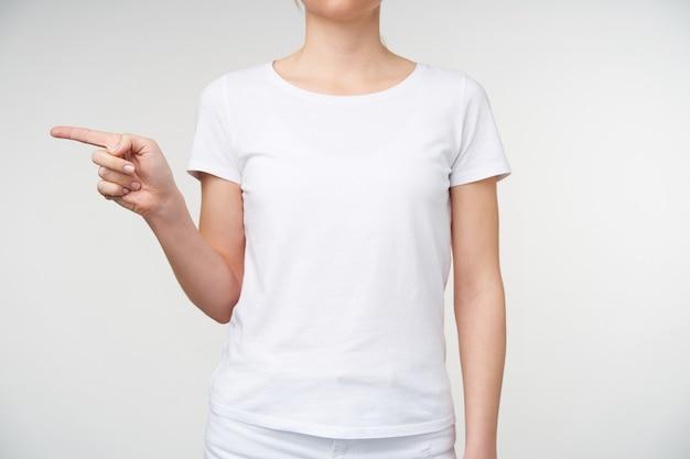 Kryty ujęcie młodej kobiety w podstawowej białej koszulce, wskazującej na bok palcem wskazującym, pokazującej literę g na języku migowym, stojącej na białym tle