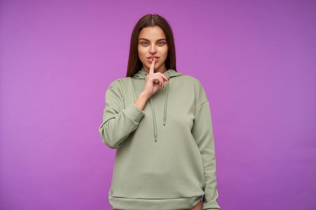 Kryty ujęcie młodej ładnej brunetki mrużącej zielone oczy, trzymając palec wskazujący na ustach, stojącej nad fioletową ścianą w miętowej bluzie z kapturem