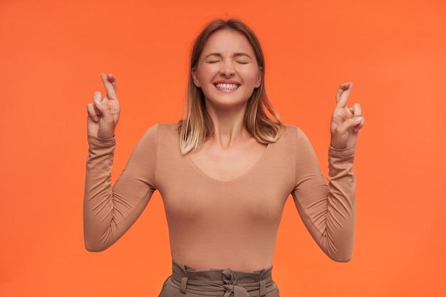 Kryty ujęcie młodej, ładnej siwowłosej kobiety trzymającej kciuki z zamkniętymi oczami i uśmiechającej się szeroko, stojącej nad pomarańczową ścianą
