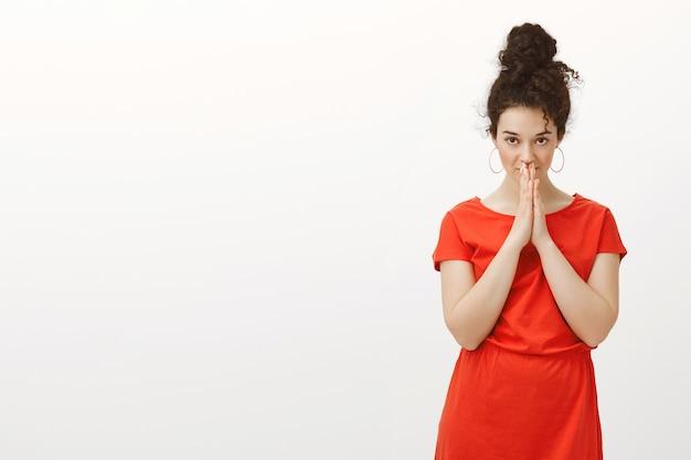 Kryty ujęcie nerwowej intensywnej atrakcyjnej kobiety w czerwonej sukience z kręconymi włosami w kok, trzymającej ręce w modlitwie nad ustami