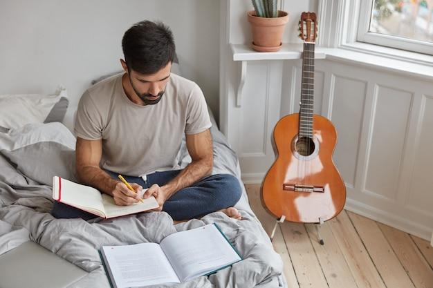 Kryty ujęcie nieogolonego młodego mężczyzny siedzącego w pozie lotosu przy niezasłanym łóżku