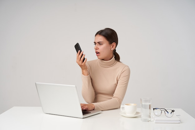 Kryty ujęcie niezadowolonej młodej brunetki patrzącej na słuchawkę z grymasem i grymasem na twarzy, trzymając dłoń na klawiaturze, siedząc na białej ścianie