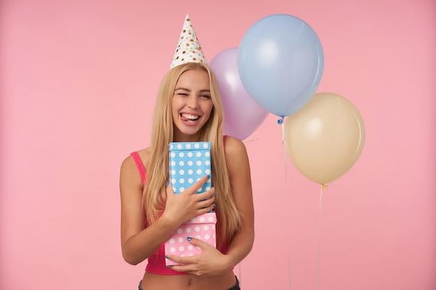 Kryty ujęcie pozytywnej młodej długowłosej kobiety radującej się podczas pozowania w wielobarwnych balonach, zabawy na przyjęciu urodzinowym i trzymania prezentów, stojąc na różowym tle