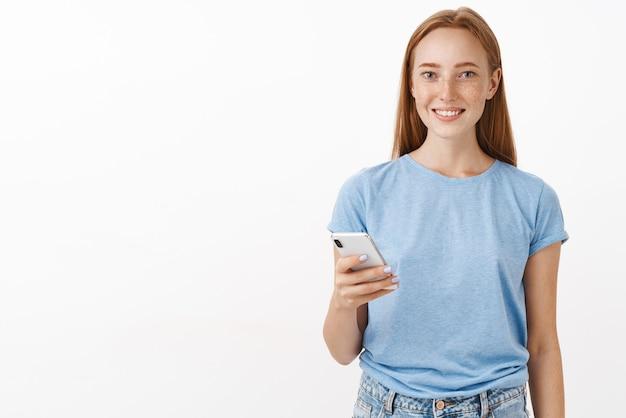 Kryty ujęcie przyjemnej, szczęśliwej i przyjaznej rudowłosej kobiety z piegami w niebieskiej casualowej koszulce trzymającej smartfona i uśmiechającej się grzecznie zapisującej numer telefonu stojący nad szarą ścianą