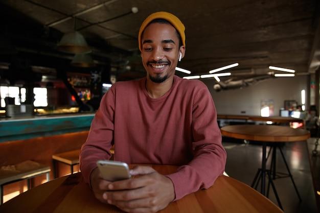 Kryty ujęcie radosnego uśmiechniętego, dość ciemnoskórego mężczyzny z brodą, pozującego nad wnętrzem kawiarni w różowym swetrze i musztardowej czapce, trzymającego telefon komórkowy w dłoniach i szczęśliwie patrząc na ekran