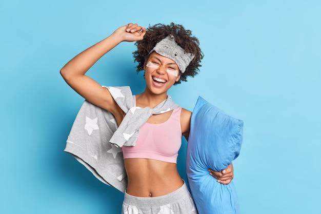 Kryty ujęcie radosnej afroamerykanki bawi się przed pójściem do łóżka tańczy beztrosko trzyma miękką poduszkę ubrana w swobodną piżamę z pochyloną głową