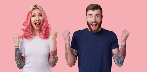 Kryty ujęcie radosnej, uroczej, wytatuowanej pary w swobodnych t-shirtach, radośnie unoszących pięści i patrzących z podekscytowaniem na aparat z szeroko otwartymi oczami i ustami, pozująca na różowym tle