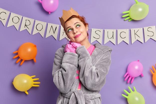 Kryty ujęcie rozmarzonej młodej kobiety skoncentrowanej nad zamyślonymi snami o wakacjach po koronawirusie nosi zwykłe ubrania odizolowane na fioletowej ścianie z dekoracjami
