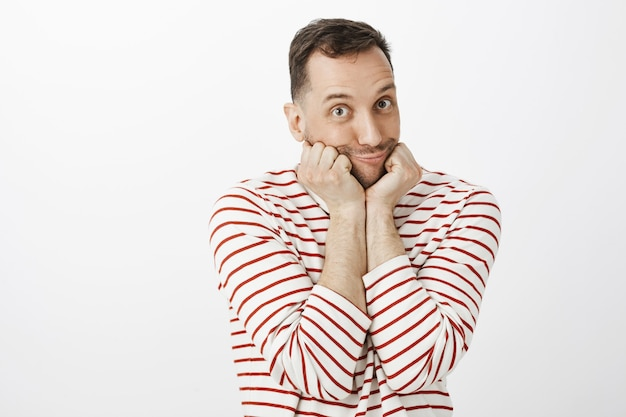 Kryty ujęcie uroczego, wzruszającego geja w pasiastym swetrze, opierającego twarz na dłoniach i robiącego delikatną kaczkę z wydymającymi wargami