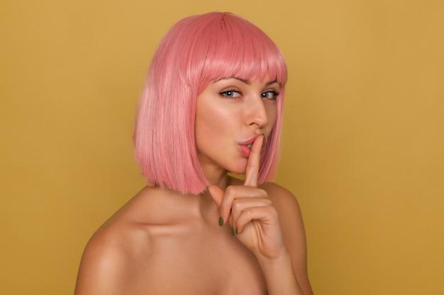 Kryty ujęcie uroczej młodej niebieskookiej różowowłosej kobiety z naturalnym makijażem, trzymając palec wskazujący na ustach, prosząc o milczenie, stojąc na musztardowym tle