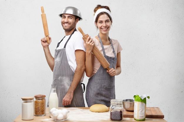Kryty ujęcie uśmiechniętych kucharzy stojących plecami do siebie, trzymając w dłoniach wałki do ciasta