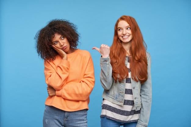 Kryty ujęcie wesołej uroczej rudowłosej kobiety pokazującej radośnie kciukiem na jej zdenerwowanej, kręconej ciemnoskórej brunetki dziewczyny, siedzącej na niebieskiej ścianie