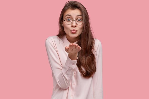 Kryty ujęcie zadowolonej kobiety o namiętnym wyglądzie wysyła pocałunek, pokazuje mwah w powietrzu, patrzy z uczuciem