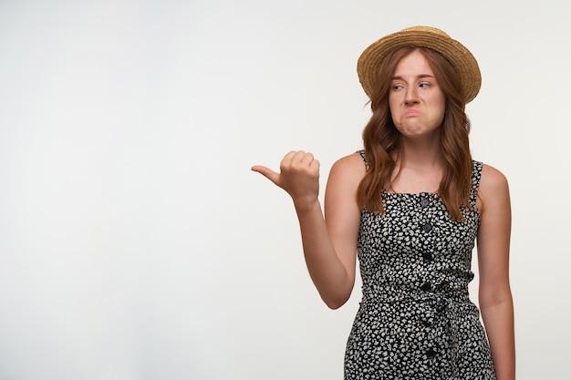 Kryty ujęcie zdenerwowanej, kręconej młodej kobiety z melancholijną twarzą pokazującą kciuk na bok, ubrana w czarno-białą sukienkę i czapkę, na białym tle