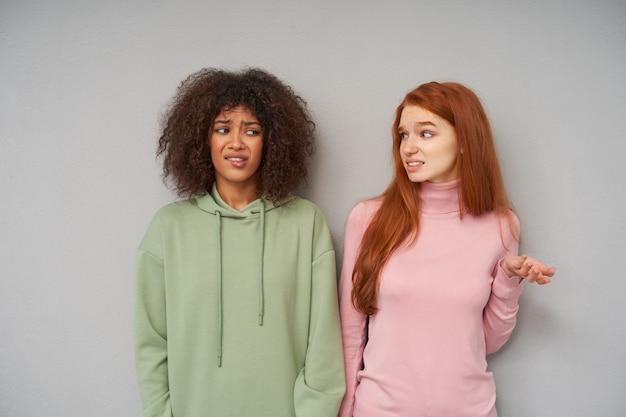 Kryty ujęcie zdezorientowanych młodych atrakcyjnych kobiet z przypadkową fryzurą pokazującą zęby i marszczone brwi, pozujących na szarej ścianie ze zdezorientowanymi twarzami