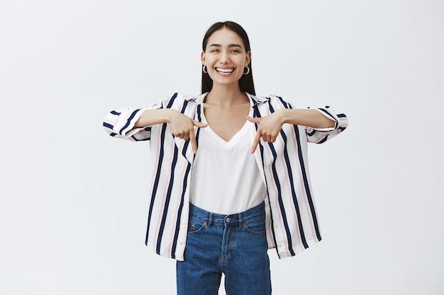 Kryty ujęcie zdumionej beztroskiej pięknej kobiety w bluzce w paski i dżinsach, śmiejącej się głośno ze szczęścia, wskazującej palcami wskazującymi w dół, pokazującej interesującą i zabawną rzecz na szarej ścianie