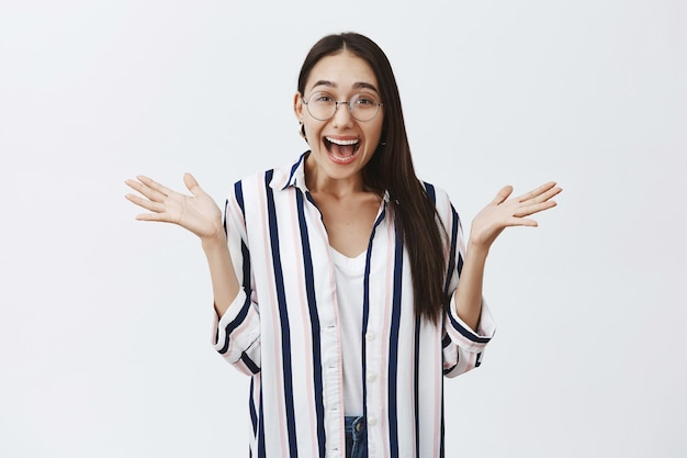 Kryty ujęcie zdumionej i podekscytowanej szczęśliwej kobiety w okularach i bluzce w paski, rozkładającej z radości dłonie i szeroko uśmiechającej się, wyjaśniającej niesamowite wieści z entuzjazmem na szarej ścianie