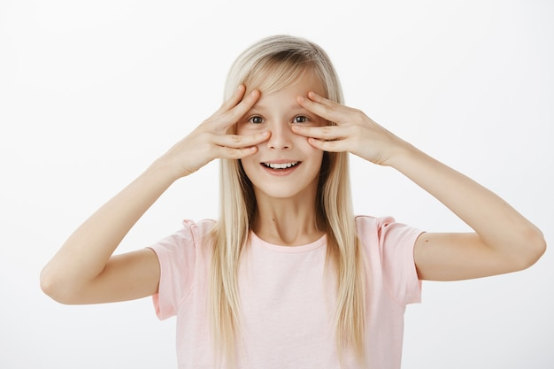 Kryty ujęcie zdumionej, zaskoczonej uroczej córki z szerokim, radosnym uśmiechem, trzymającej palce blisko oczu i uśmiechającej się z pozytywnej sceny, radosnej, uczestniczącej w wielkim przyjęciu na jej cześć nad szarą ścianą