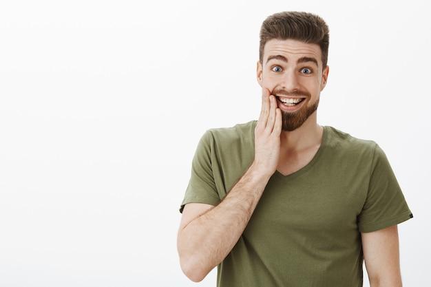 Kryty ujęcie zdziwionego, szczęśliwego i podekscytowanego przystojnego mężczyzny, całującego się w policzek, podekscytowanego i optymistycznego, dotykającego twarzy z uniesionymi dłońmi brwiami i uśmiechającego się ze szczęścia na białej ścianie