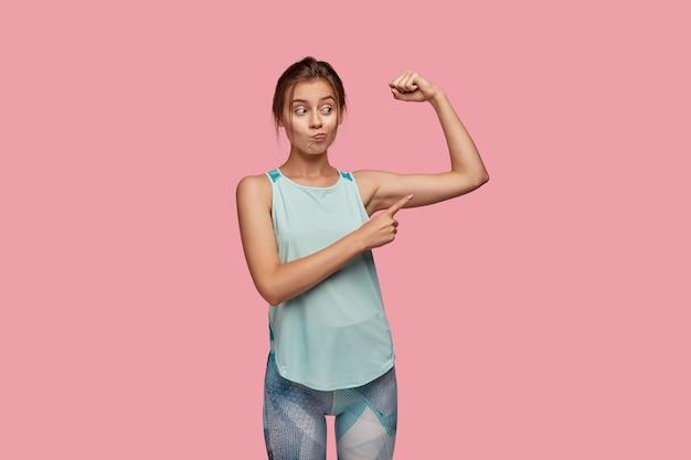 Kryty ujęcie zdziwionej młodej kobiety zaciska usta z niezadowoleniem, podnosi prawą rękę i wskazuje na bicepsy, niezadowolona ze złych wyników treningu, chce mięśni, pozuje nad różową ścianą.