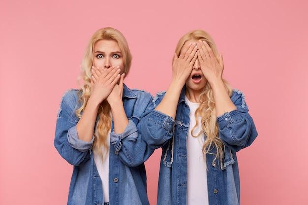 Kryty ujęcie zszokowanych młodych ładnych sióstr z luźnymi kręconymi włosami zakrywającymi uszy i usta z uniesionymi dłońmi, stojąc na różowym tle w codziennych ubraniach