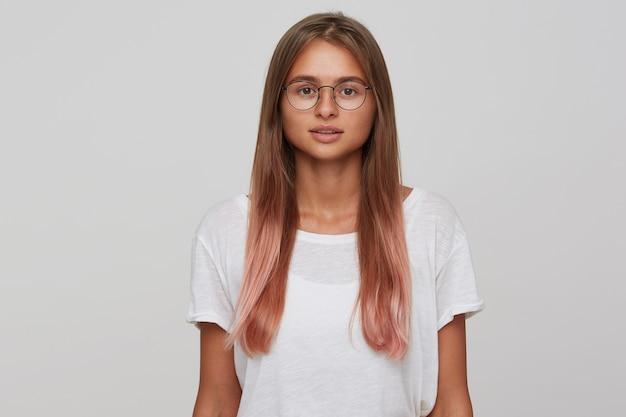 Kryty zdjęcie pięknej młodej kobiety z jasnobrązowymi długimi włosami w okularach, pozując na białej ścianie z opuszczonymi rękami, patrząc ze spokojną twarzą