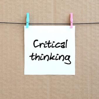 Krytyczne myślenie. uwaga jest zapisana na białej naklejce, która wisi na spinaczu na linie na tle brązowej tektury