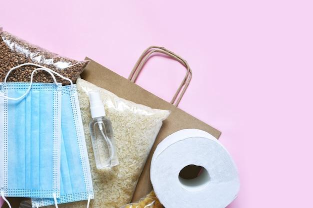 Kryzys dostaw żywności na różowym tle. makaron, kasza gryczana, maska, środek antyseptyczny, papier. darowizna. płasko jedzenie.
