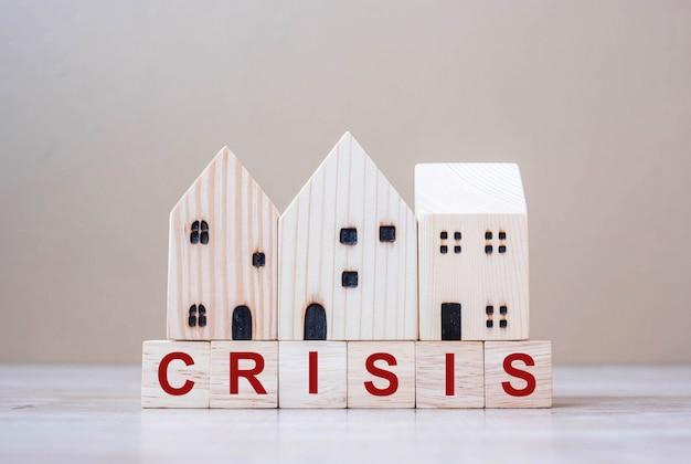 Kryzys sześcian bloki z drewnianym domem modelują na stołowym tle.