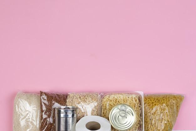 Kryzysowe dostawy żywności na okres izolacji kwarantannowej koronawirusa, ryżu, makaronu, płatków owsianych, żywności w puszkach, papieru toaletowego, gryki, bananów na różowym tle