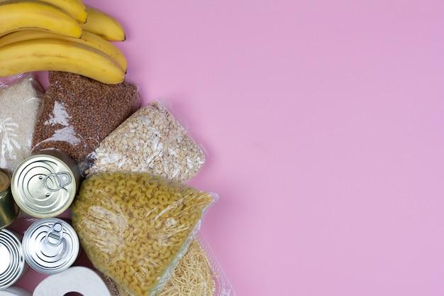 Kryzysowe dostawy żywności na okres izolacji kwarantanny koronawirusa, ryżu, makaronu, płatków owsianych, żywności w puszkach, papieru toaletowego, gryki na różowym tle