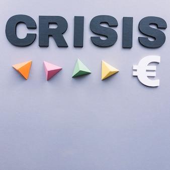 Kryzysu słowo z kolorowymi trójgraniastymi ostrosłupami i euro podpisujemy na popielatym tle