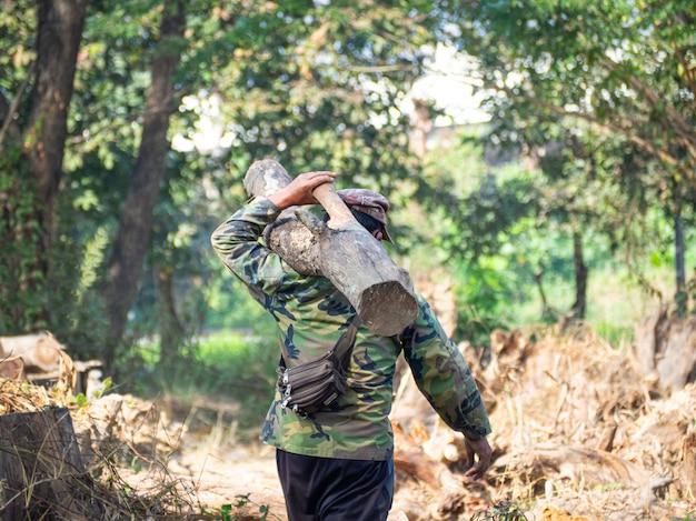 Krzepki mężczyzna w kapeluszu i koszuli z długimi rękawami, spacerując po lesie, niósł na ramionach kawałek drewna
