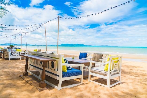 Krzes? oi stół jadalnia na plaży i morza z błękitne niebo