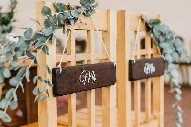 Krzesła dla pary młodej ozdobione kwiatami z napisami pan i pani na ceremonię ślubną