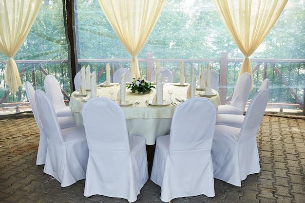 Krzesła i okrągły stół dla gości podawane ze sztućcami, kwiatami i naczyniami i przykryte obrusem
