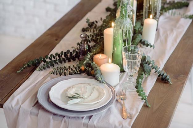 Krzesła i stół dla gości, ozdobione świecami, podawane ze sztućcami i naczyniami i przykryte obrusem.