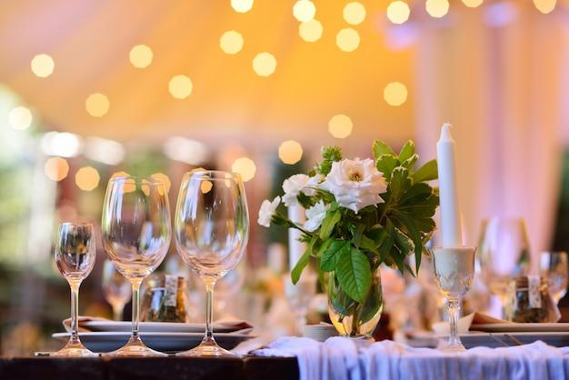 Krzesła i stół dla gości, ozdobione świecami, podawane ze sztućcami i zastawą stołową