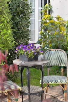 Krzesła i stół na drewnianym tarasie w ogrodzie wiejskiego domu