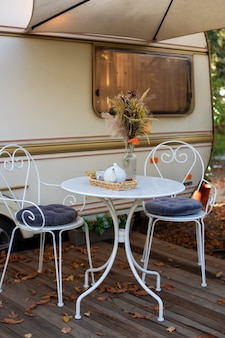 Krzesła i stolik z zestawem do herbaty ustawione przed przytulną przyczepą kempingową retro na trawniku