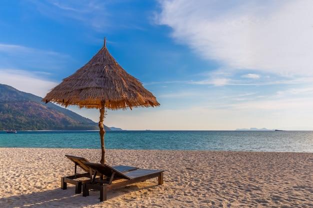 Krzesła plażowe, parasol i palmy na pięknej plaży na wakacje i relaks na wyspie koh lipe w tajlandii