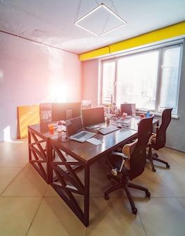 Krzesła przy drewnianym nowoczesnym stole z laptopami. szerokie okno i żółty akcent nad nim. jasne naklejki na niebieskiej ścianie. koncepcja wnętrza biura.