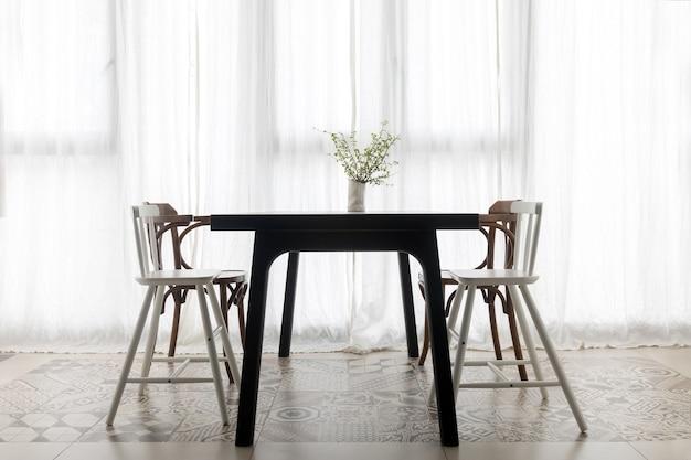 Krzesła umieszczone przy stole jadalnym z bukietem kwiatów w wazonie przy oknie z białą zasłoną w nowoczesnym mieszkaniu w stylu minimalistycznym