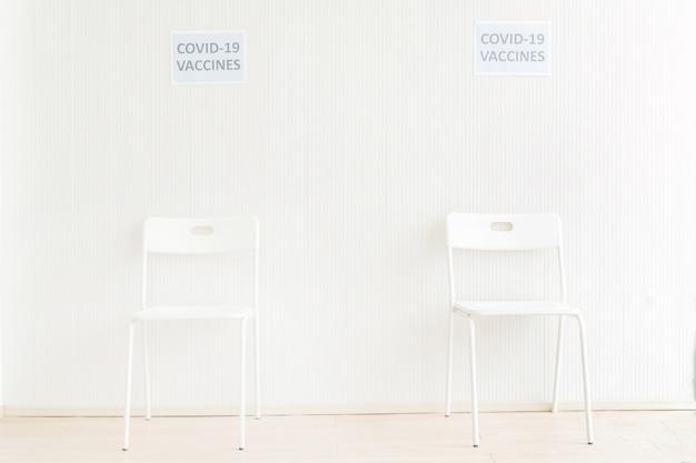 Krzesła ustawione w poczekalni, aby otrzymać szczepionkę przeciw krukowicom w szpitalu z białym tłem ściennym